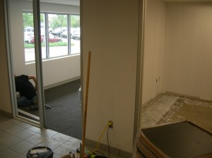 Carpet install underway in an office while glue dries in another.