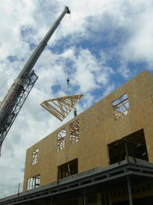Roof trusses swing above 3rd floor framing.