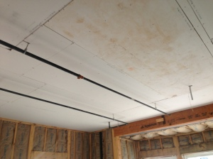 Sheetrock underside of fire-rated floor-ceiling assembly.